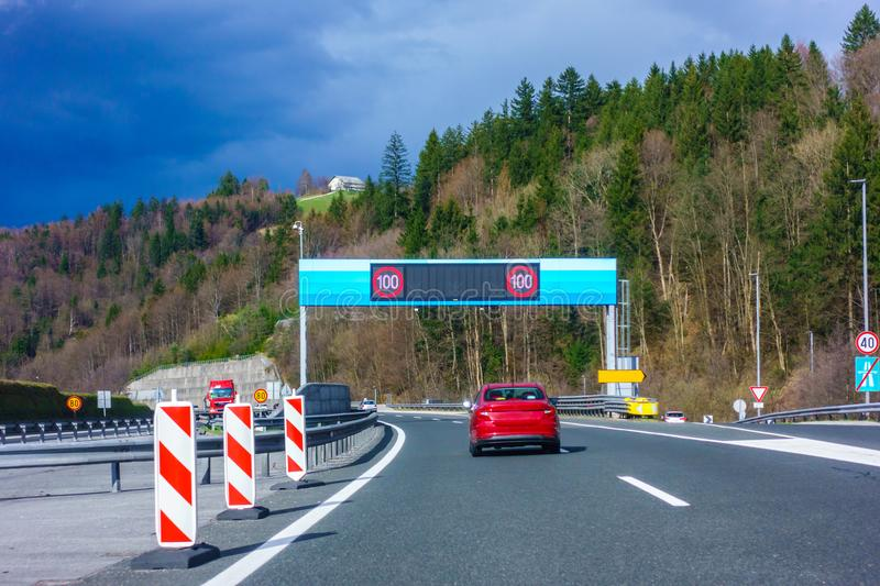 Modern LED traffic signs on highway, red car, truck on road. Modern LED traffic signs on Slovenian highway A1 near Trojane, red car, truck on road stock images