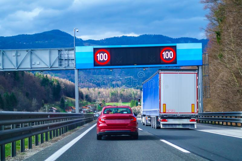 Modern LED traffic signs on highway, red car, truck on road royalty free stock photos