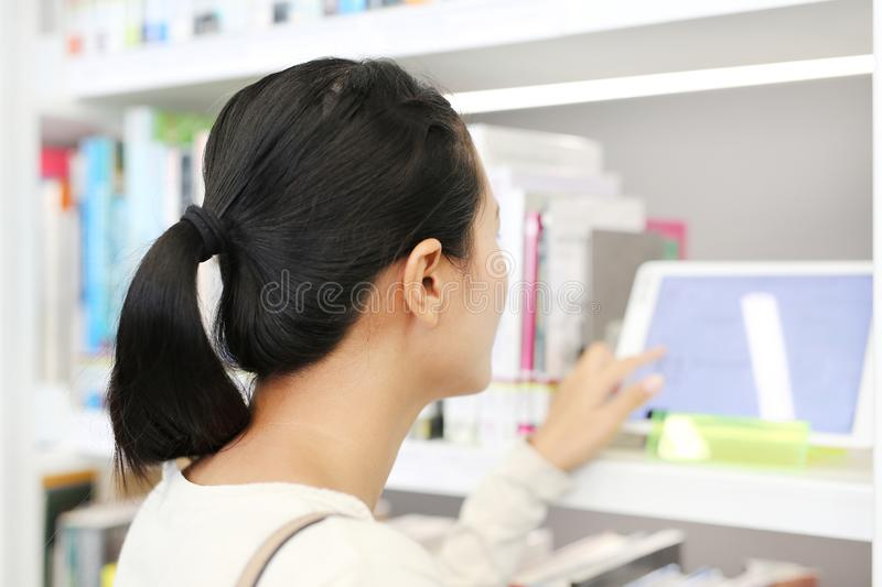 Modern library, Asian woman Search the database from the tablet stock images