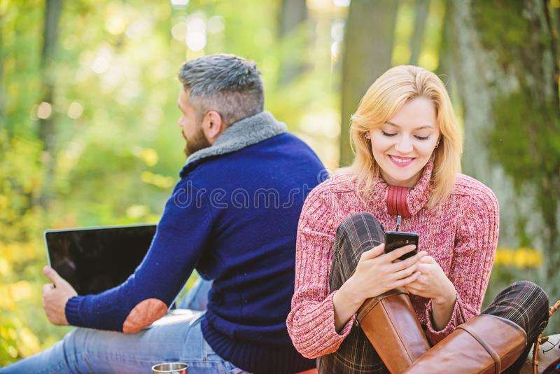 Modern life. Happy loving couple relaxing in park with mobile gadgets. Modern people always involved online. Communication. Internet addiction. Online life royalty free stock photos
