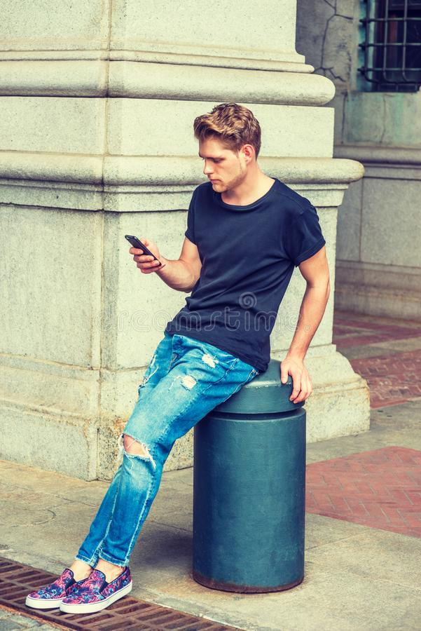 Modern daily life. Young American Man with little beard texting on cell phone in New York, wearing black T shirt, destroyed jeans, fashionable shoes, sitting royalty free stock image