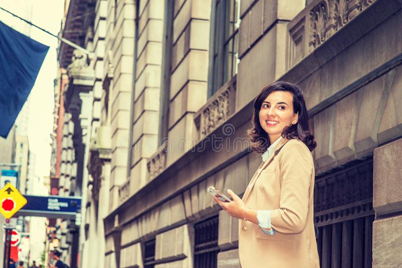 Modern Daily Life of Old City. Young American Woman traveling in New York City, wearing beige blazer, holding cell phone, walking on old style street with high royalty free stock photos