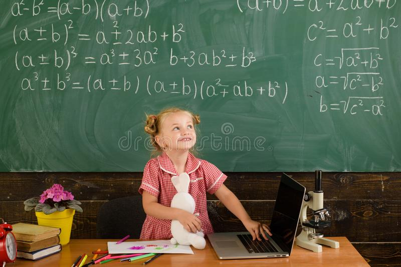 Modern life in school. Happy girl use new technology for online education as part of modern life. Little child smile. With laptop computer at chalkboard royalty free stock image