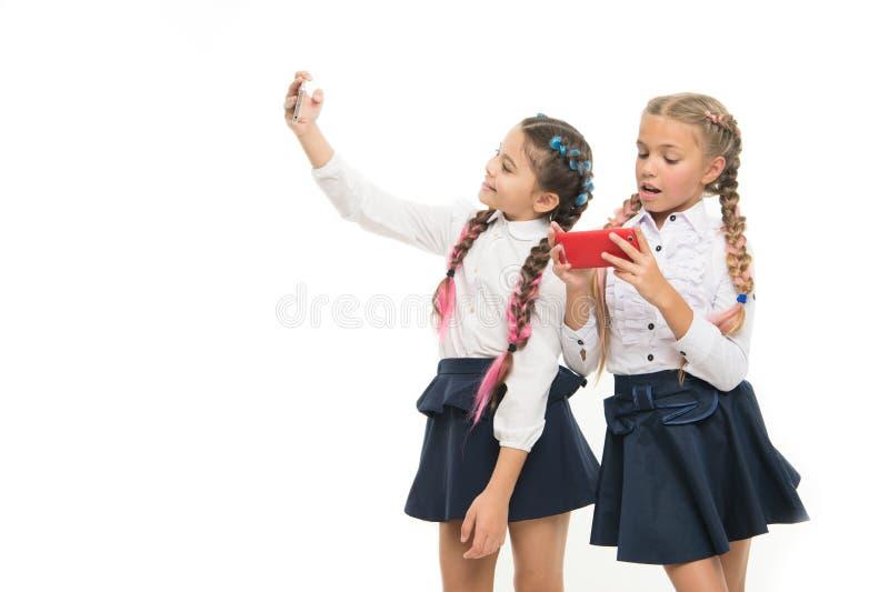Modern life. Schoolgirls use mobile internet smartphone. School application smartphone. Mobile addiction. Worldwide net. Internet resource has hazards for kids royalty free stock images