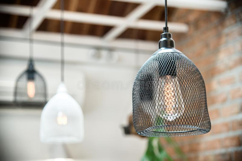Modern light bulb hanging in the vintage coffee shop interior background stock photos
