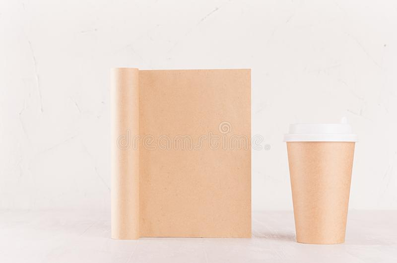 Modern light concept design for restaurant and coffee shop advertising - kraft brown paper cup and blank notebook on white wood. stock photography