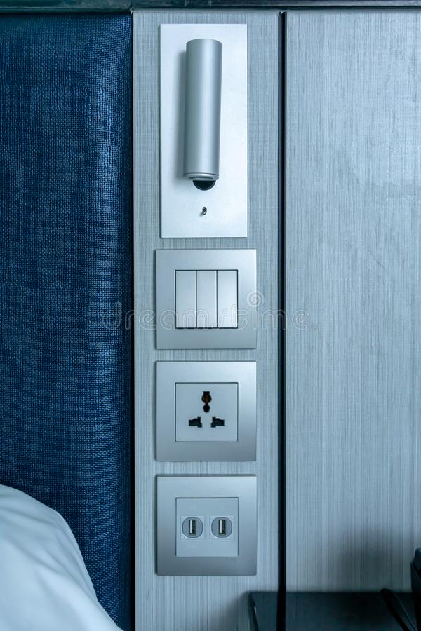 Modern light, light switch, electric plug and usb chargers against wooden wall stock photo