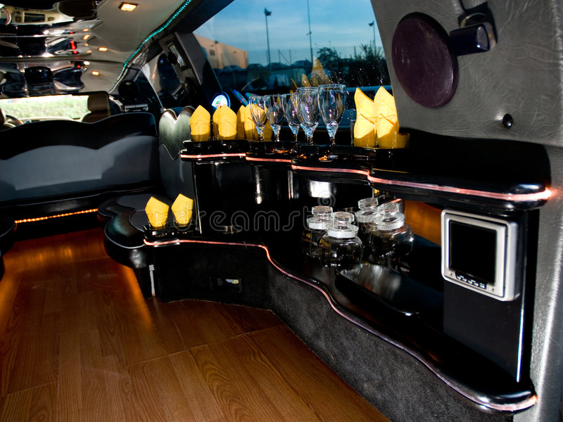 Modern limousine interior. Cocktail bar inside modern limousine stock image