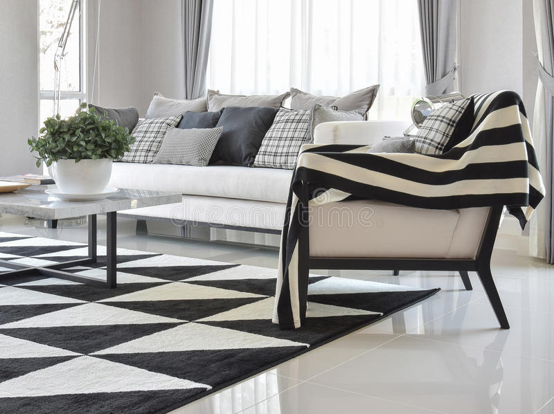 Modern living room interior with black and white checked pattern pillows and carpet. Modern living room with black and white checked pattern pillows and carpet stock photos
