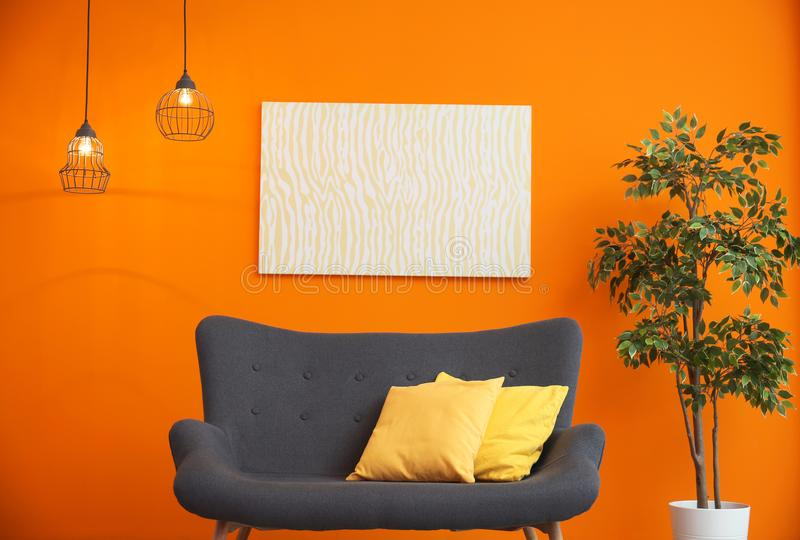 Modern living room interior with comfortable sofa near color wall. Modern living room interior with comfortable gray sofa near color wall stock photos
