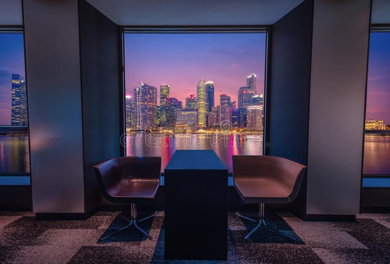 Modern living room with view Singapore skyline at sunset.  stock images
