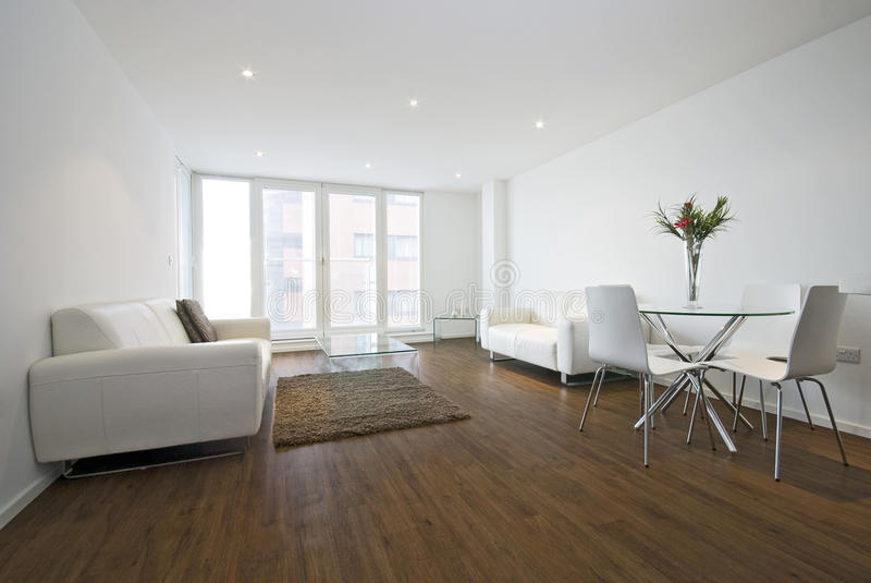 Modern living room with white leather sofas. And a dining table for four stock photo