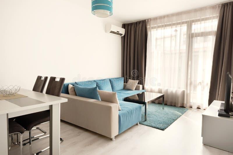 Modern ljus och hemtrevlig vardagsruminredesign med soffan och att äta middag tabellen och kök Grå färg- och turkosblåttstudioläg arkivbilder