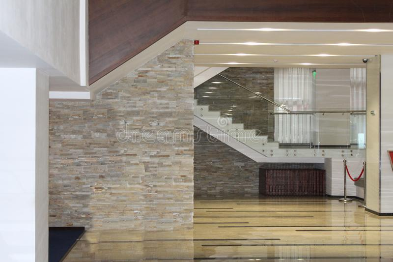 Modern lobby. Hall, marble staircase, stairs. Entrance hall of the hotel. Tile floor and stone wall stock image