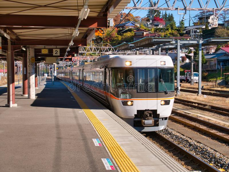 A modern, local, electric commuter train arrives at an empty platform at Kiso Fukushima Station stock images
