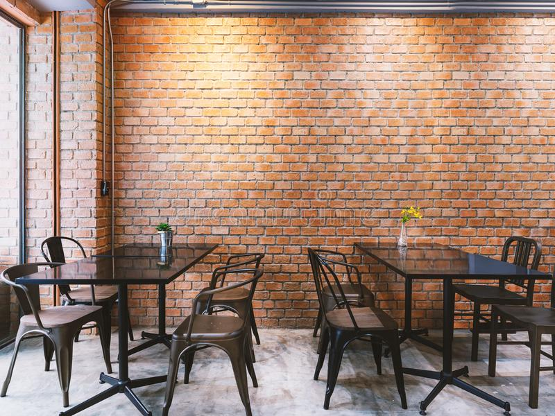Modern loft style cafe with black table set and brick wall royalty free stock image