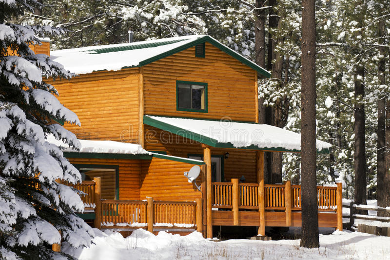 Modern Log Cabin Home In The Winter Woods. New modern log cabin home in the snowy woods of the White Mountains in mid-eastern Arizona, USA royalty free stock image