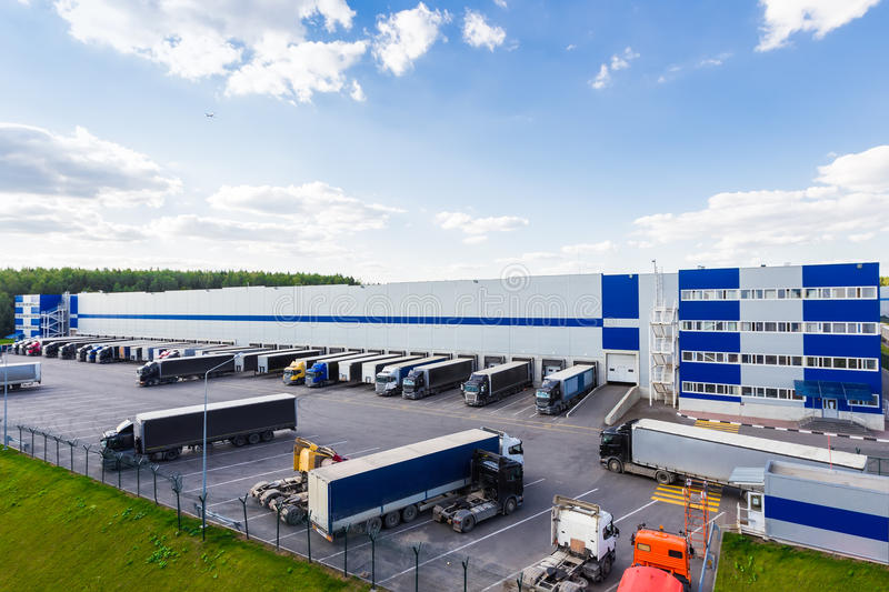 Modern logistics center. Modern warehouse during business hours with a lot of different cargo truck royalty free stock images