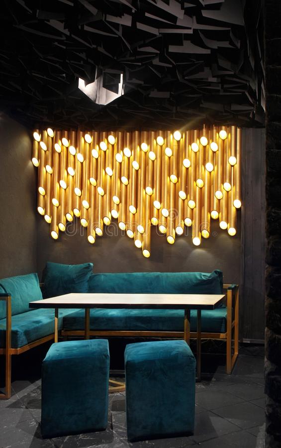 Modern lounge bar interior.Dark tone.Dark cyan sofa and chairs.Golden laterns in form of tubes stock photography