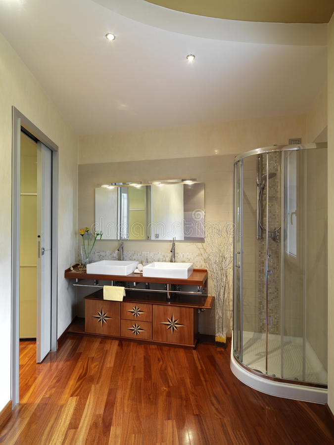 Modern and luxurious bathroom. With wood floor and wood furniture near the shower cubicle royalty free stock images