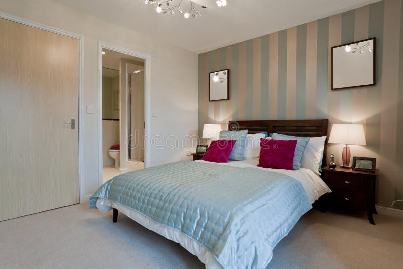 Modern luxury bedroom. Fashionable modern luxury bedroom dressed with opulent fabrics stock photo