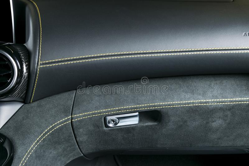 Modern Luxury car inside. Interior of prestige modern car. A/C Ventilation system. Black perforated leather cockpit with yellow. Stitching. Steering wheel and stock images