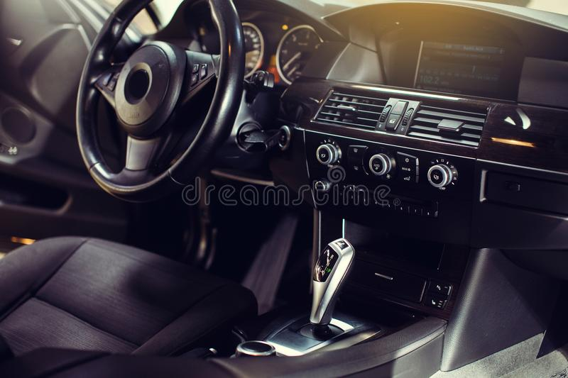 Modern luxury car Interior - steering wheel, shift lever and dashboard. Car interior luxury inside. Steering wheel, dashboard, speedometer, display stock photography