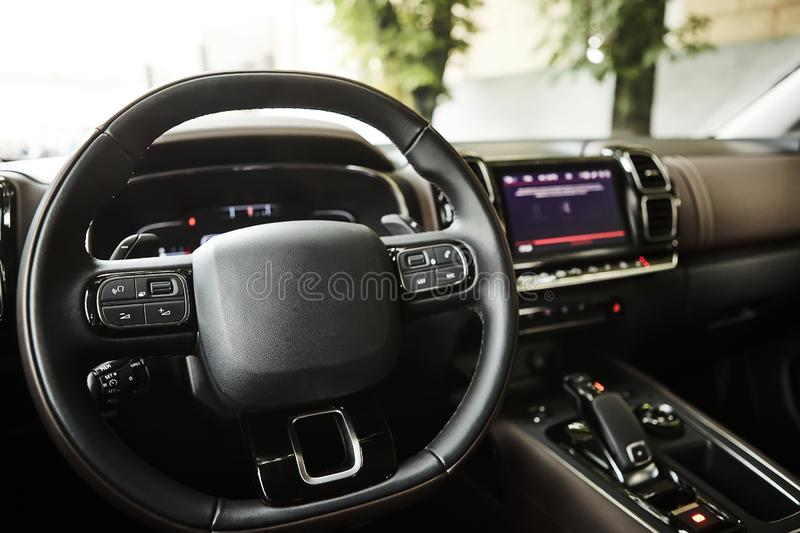 Modern luxury car Interior - steering wheel, shift lever and dashboard. Car interior luxury inside. Steering wheel. Dashboard, speedometer, display. Black royalty free stock images