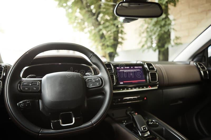 Modern luxury car Interior - steering wheel, shift lever and dashboard. Car interior luxury inside. Steering wheel. Dashboard, speedometer, display. Black stock photos