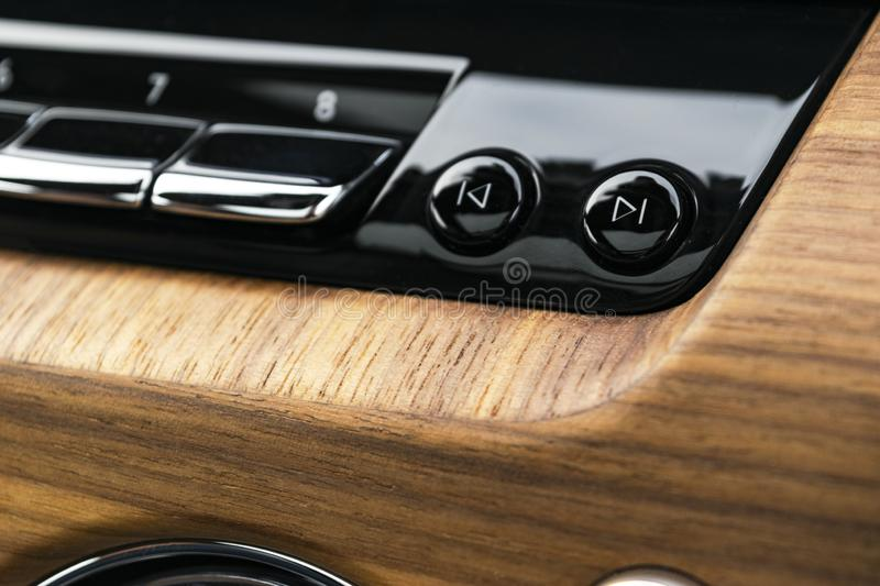 Modern luxury car white interior with natural wood panel. Part of car dashboard. Interior of prestige modern car. Media control bu royalty free stock photo