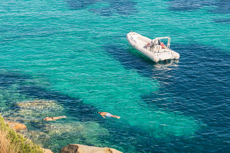 Modern luxury dinghy on turquoise sea with clear blue water. Modern luxury dinghy on turquoise sea in tropical island - People snorkeling in exclusive exotic stock images