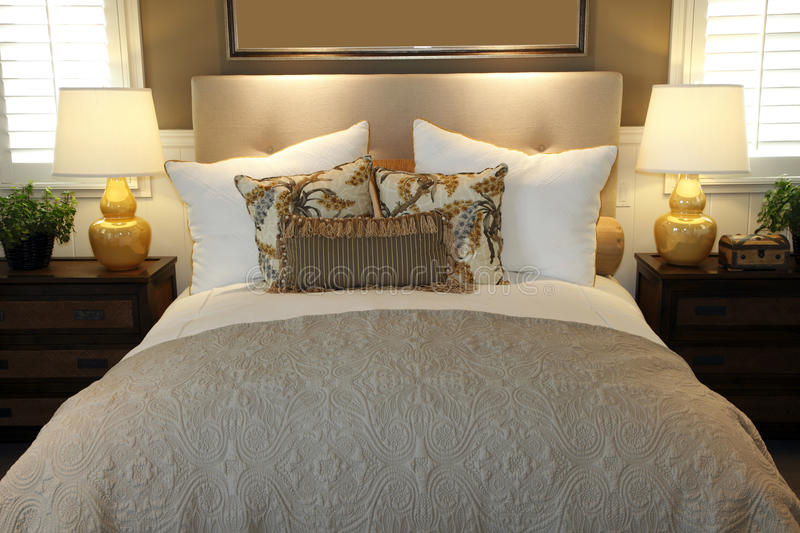 Modern luxury home bedroom. Luxury home bedroom with stylish pillows and decor royalty free stock photography