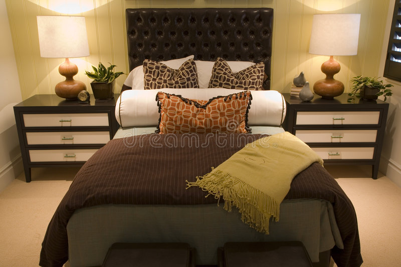 Modern luxury home bedroom. Luxury home bedroom with stylish furniture and decor royalty free stock image