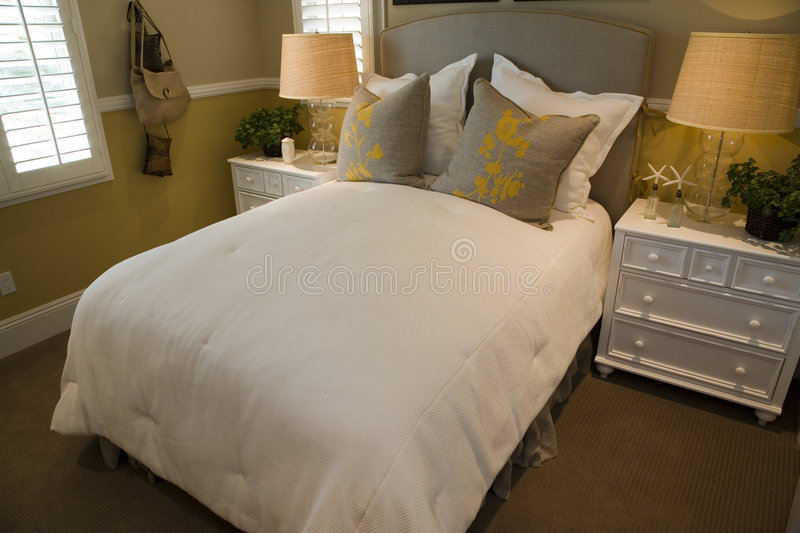 Modern luxury home bedroom. Luxury home bedroom with stylish furniture and decor royalty free stock photography