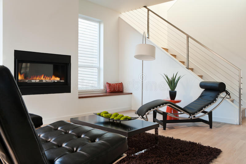 Modern Luxury Living Room. Horizontal shot of a modern living room in an upscale home with lounge chairs, and view of stairs and fireplace stock images