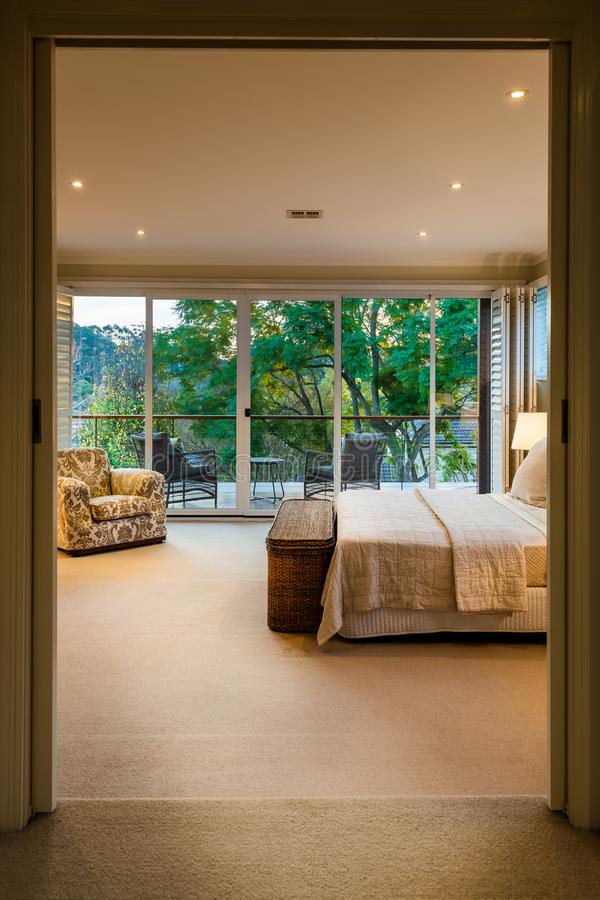 Modern luxury master bed room with bed side tables, lamps, down lights and walk in robe, real estate. Modern luxury master bed room with bed side tables, lamps stock images