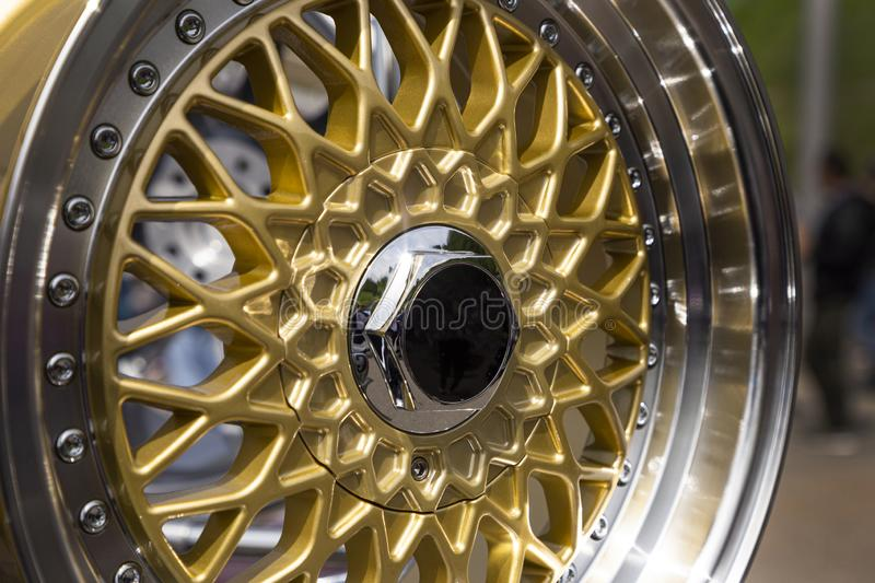 Modern luxury metal alloy wheel for cars. Showcase with gold colored rims. Closeup side and front view. stock photos