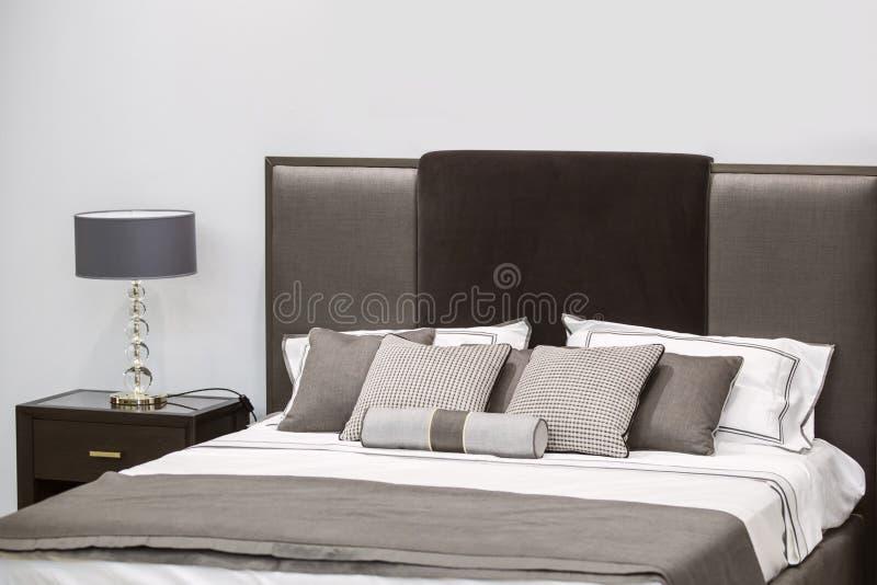 Modern lyxig inre av sovrummet Design av ett rum i ett hotell med en lampa för säng och för original- tabell royaltyfria bilder