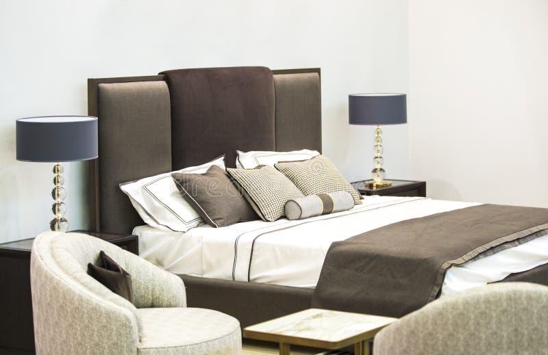 Modern lyxig inre av sovrummet Design av ett rum i ett hotell med en säng och lampor för original- tabell royaltyfri bild