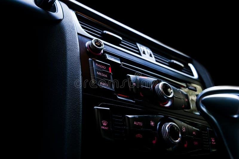 Modern lyxig sportbil inom Inre av prestigebilen black läder Specificera för bil instrumentbräda Massmedia, klimat och navigering royaltyfri fotografi