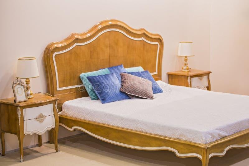Modern lyxig träinre av sovrummet Design av ett rum i ett hotell med en säng och lampor för original- tabell royaltyfria foton