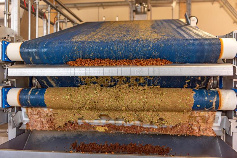 Modern Machine squeezes apples and apple pomace remain as press residues. Machine squeezes apples and apple pomace remain as press residues royalty free stock image