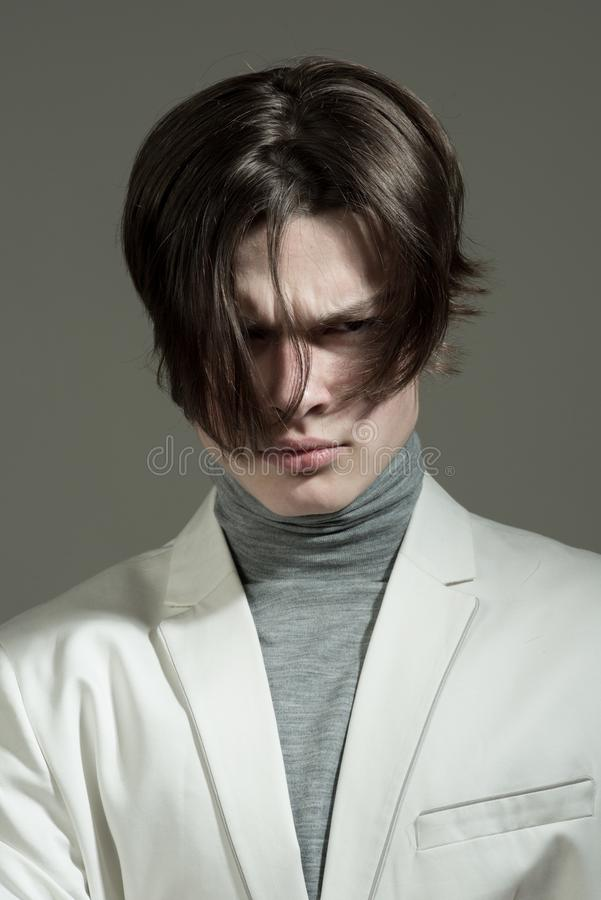 Modern male. Hair style and skincare. Beauty and fashion. Man with trendy look. Fashion man with mystery look. Glamour. Fashion model. serious or sad guy with stock images