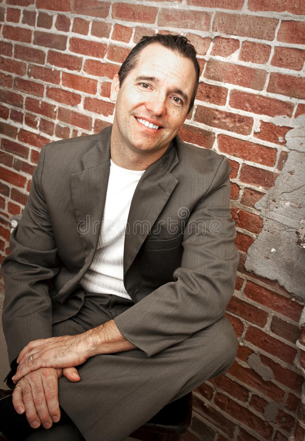 Modern man. A portrait of a confident, smiling man sitting in a chair in front of brick wall royalty free stock photography