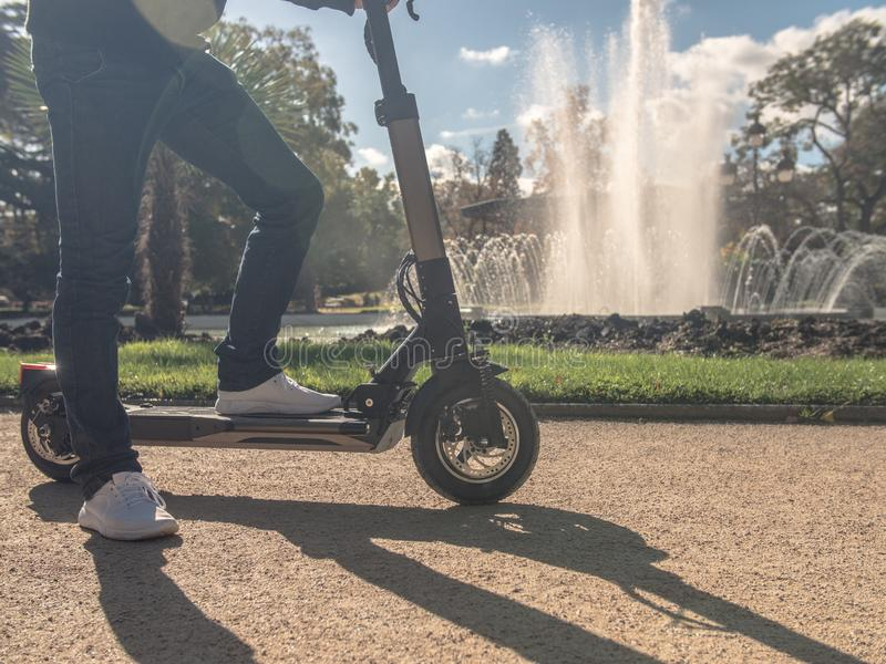 Modern Man on Electric Scooter in Sunny Park with Fountain 2 stock photography