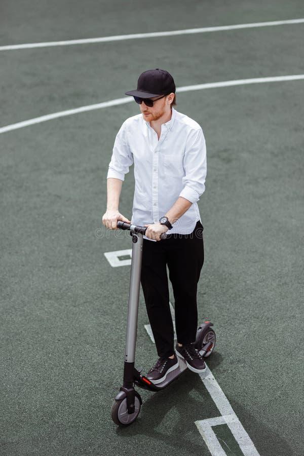 Modern man i stilfull svartvit dräkt som rider den elektriska sparkcykeln i staden arkivbild