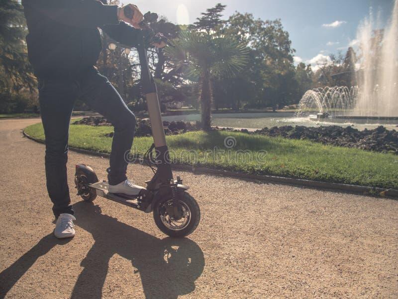 Modern man på den elektriska sparkcykeln i Sunny Park med springbrunn 1 arkivbilder