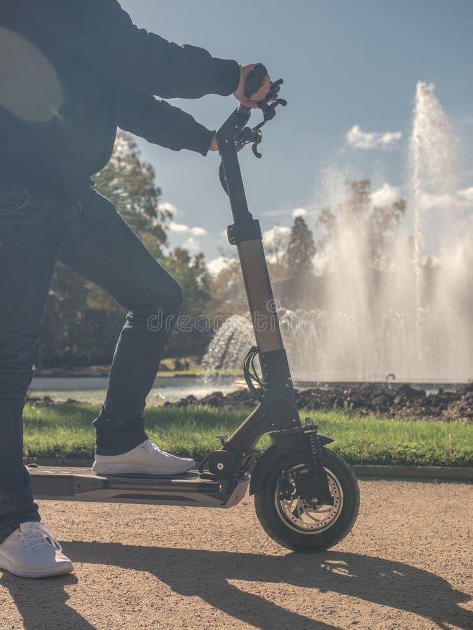 Modern man på den elektriska sparkcykeln i Sunny Park med springbrunn 4 royaltyfri fotografi