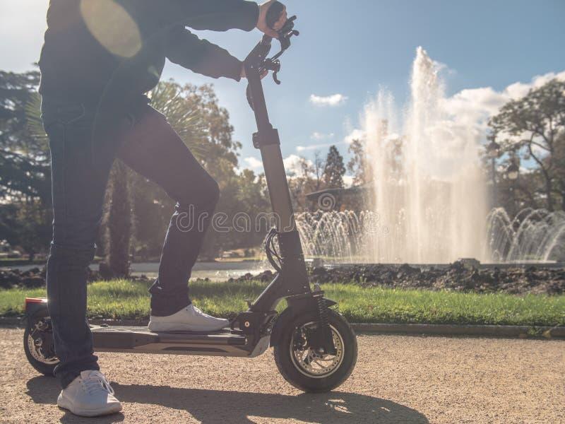 Modern man på den elektriska sparkcykeln i Sunny Park med springbrunn 3 royaltyfria foton