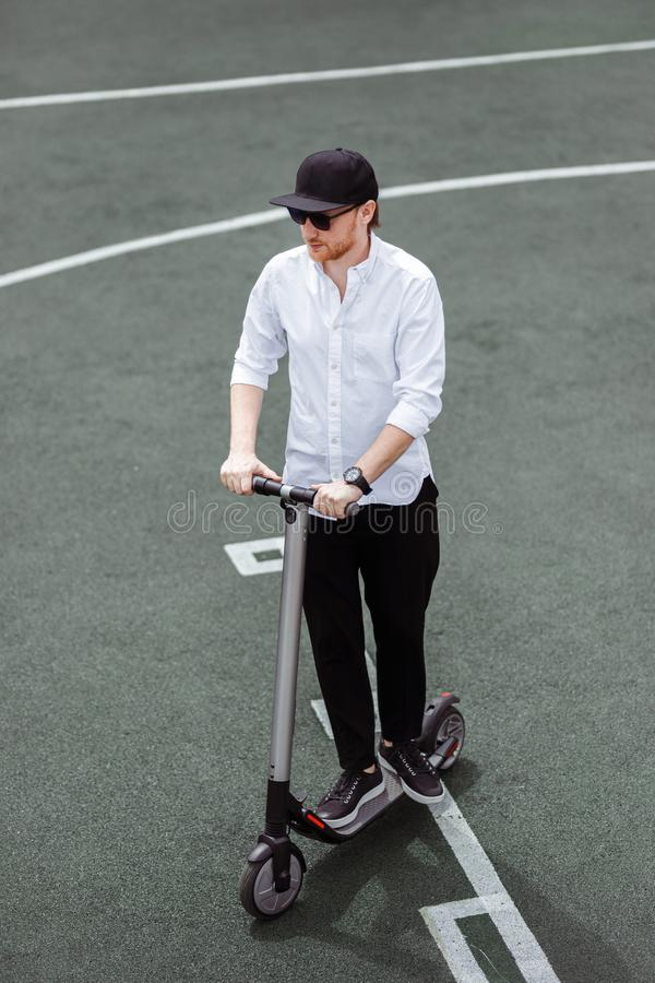 Modern man in stylish black and white outfit riding electric scooter in the city.  stock photography